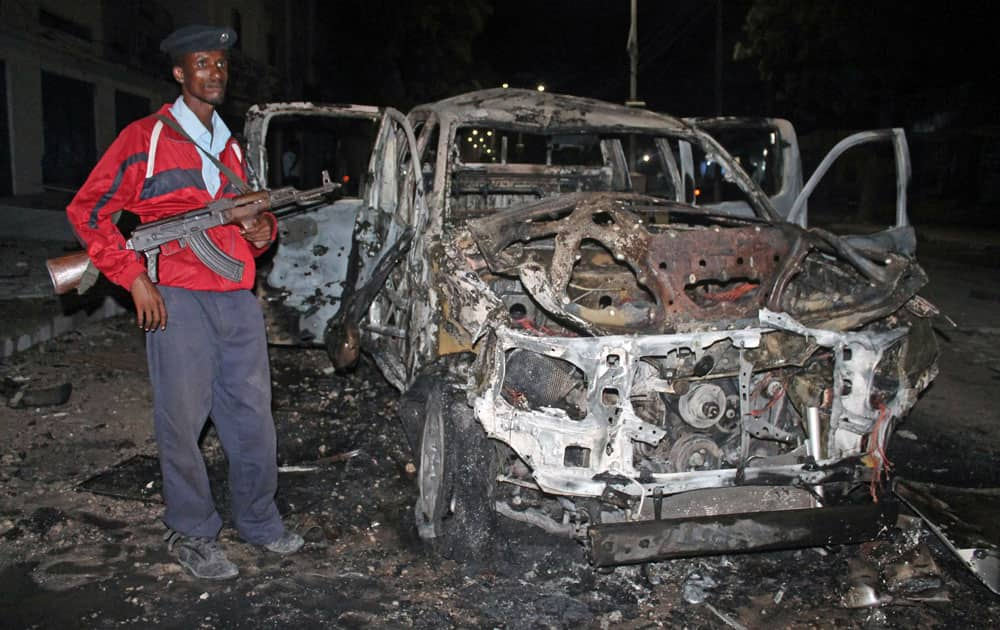 A Somali soldier stands near a destroyed car after a bomb attack in Mogadishu, Somalia.