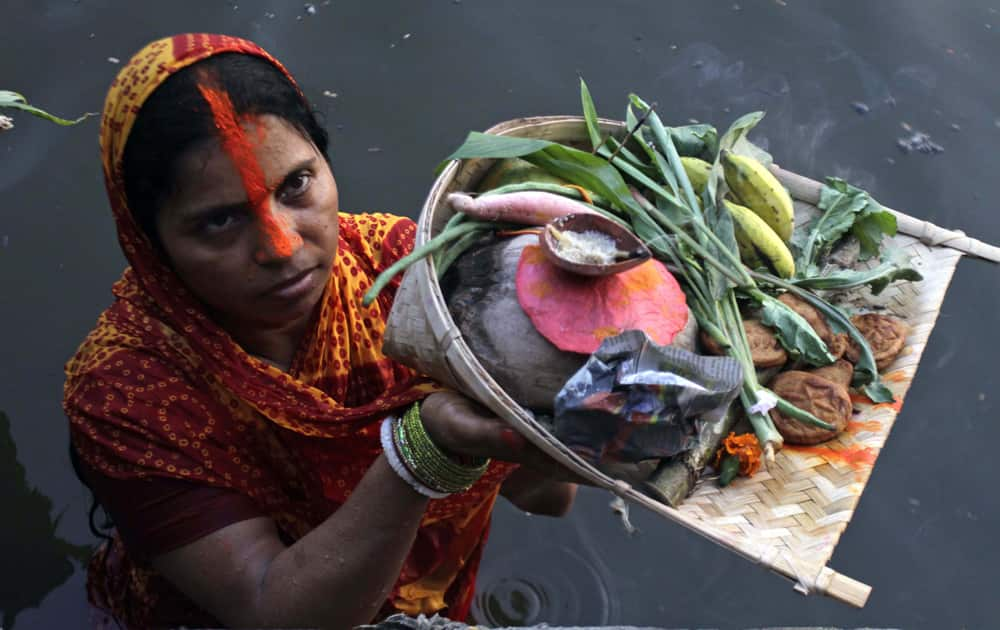 A Hindu woman devotee performs rituals during the Chhath Puja festival at a lake in Kolkata.