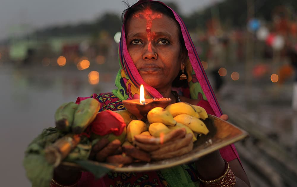 A Hindu devotee performs rituals to the setting sun in the River Brahmaputra during Chhath Puja festival in Gauhati.