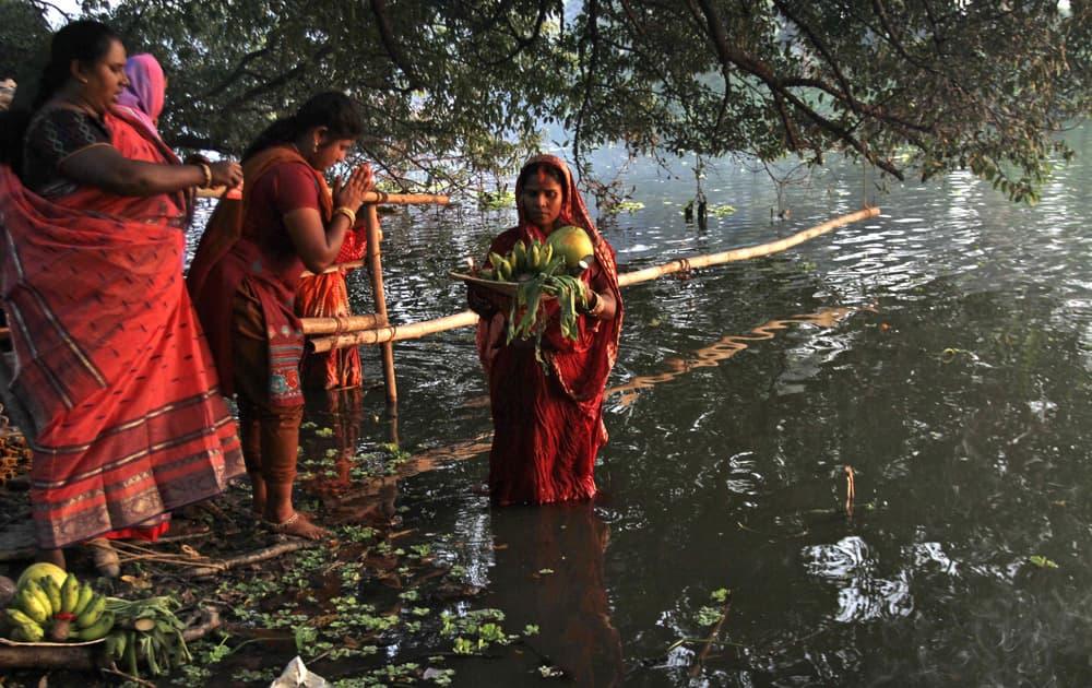 Hindu women devotees perform rituals during the Chhath Puja festival at a lake in Kolkata.