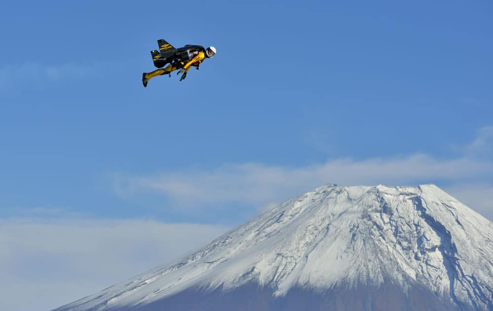 Yves Rossy, known as the Jetman, flies over the snow-capped peak of Mount Fuji, Japan, during his first flight in Asia..
