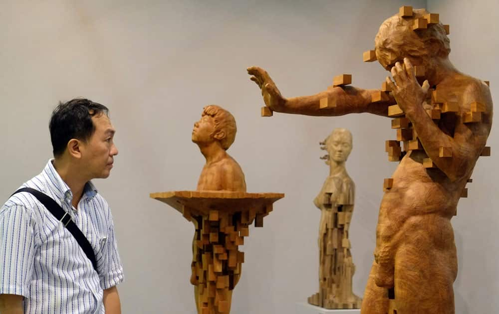 A visitor looks at a wood carving by Taiwanese artist Donald Harn entitled