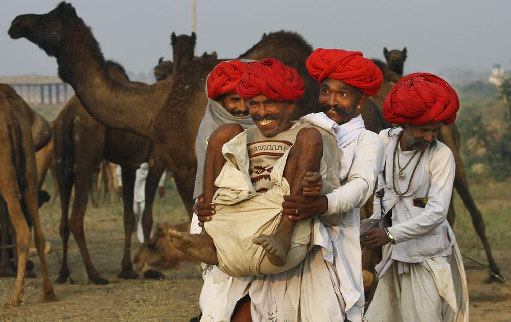 A camel herder lifts another while playing around during the annual cattle fair in Pushkar, Rajasthan.