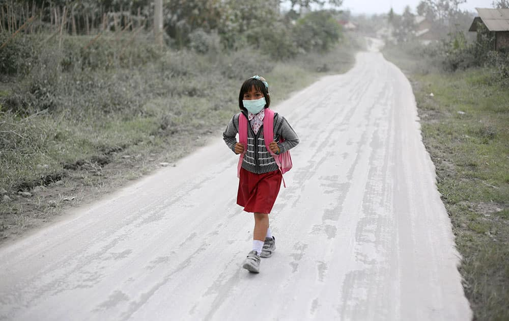 A student walks on a road covered with volcanic ash from the eruption of Mount Sinabung in Tiga Nderket, North Sumatra, Indonesia.