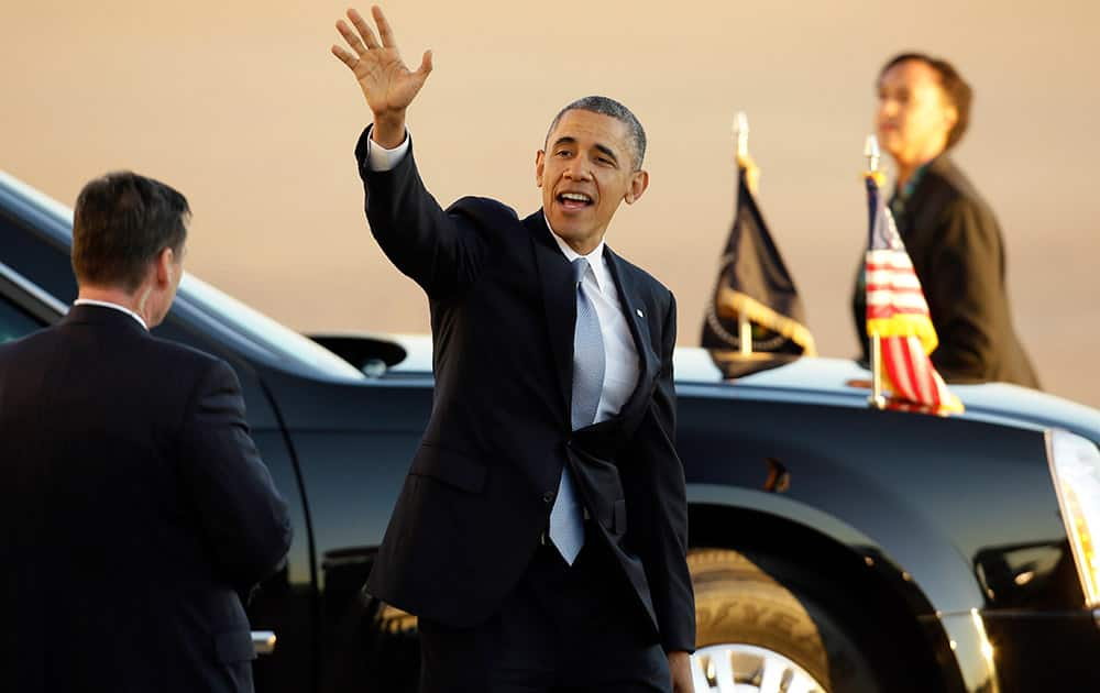 President Barack Obama waves as he departs Love Field Airport after shaking hands with supporters following his arrival at Love Field Air Port, in Dallas.