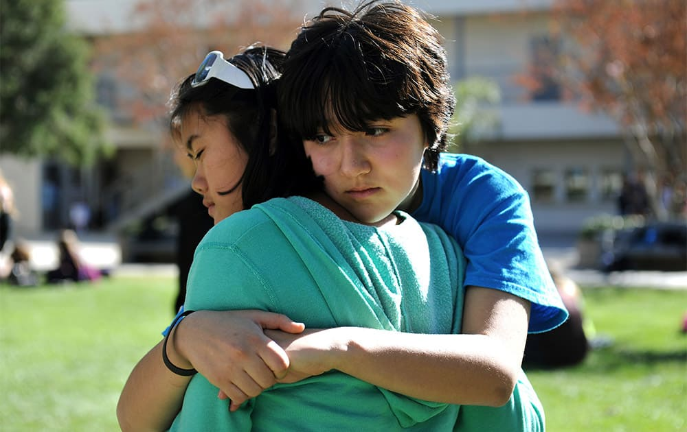 Calabasas High School students Aya McGlothlin, right, and Meili Spano embrace following a rally to support teacher Brian Ludmer at the school.