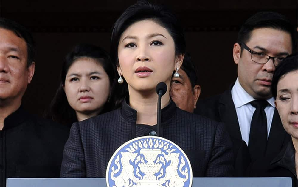 Thailand Prime Minister Yingluck Shinawatra, center, flanked by Cabinet ministers and aides, speaks during a news conference at the government house in Bangkok, Thailand.