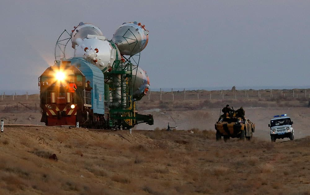 Russian police guard the Russia`s booster rocket Soyuz-FG with the space capsule Soyuz TMA-11M that will carry new crew to the International Space Station (ISS) as the rocket is transported from hangar to the launch pad at the Russian leased Baikonur cosmodrome, Kazakhstan.