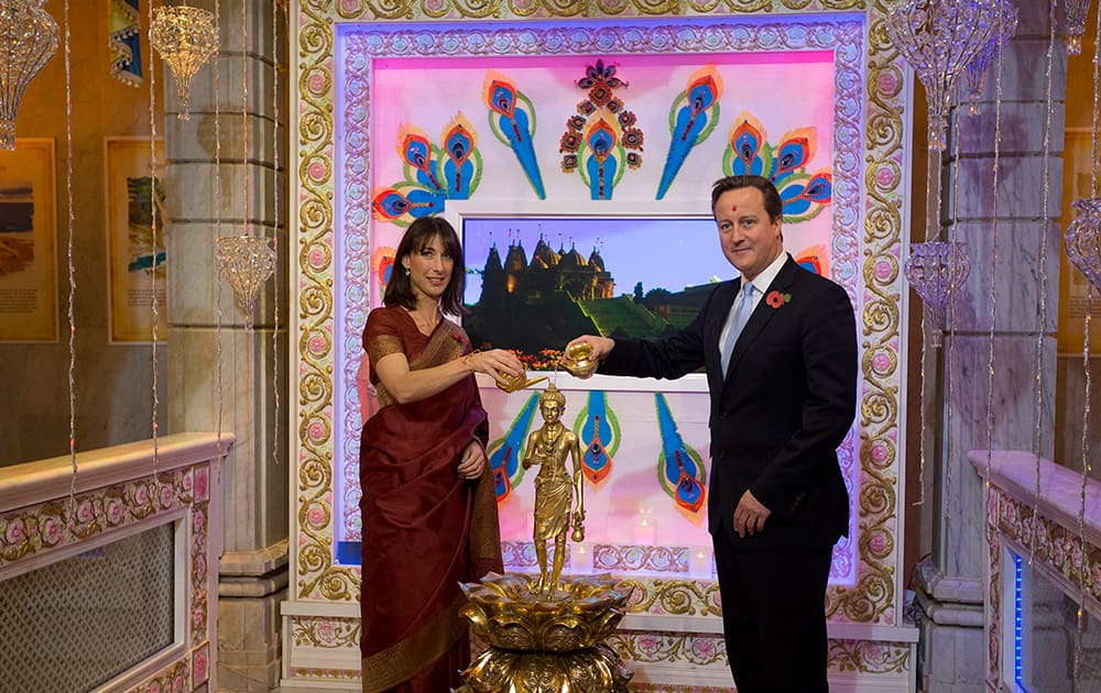 Britain`s Prime Minister David Cameron and his wife Samantha pour water on a Hindu deity as they arrive for a visit to the Hindu temple the Shri Swaminarayan Mandir in London, during Diwali.