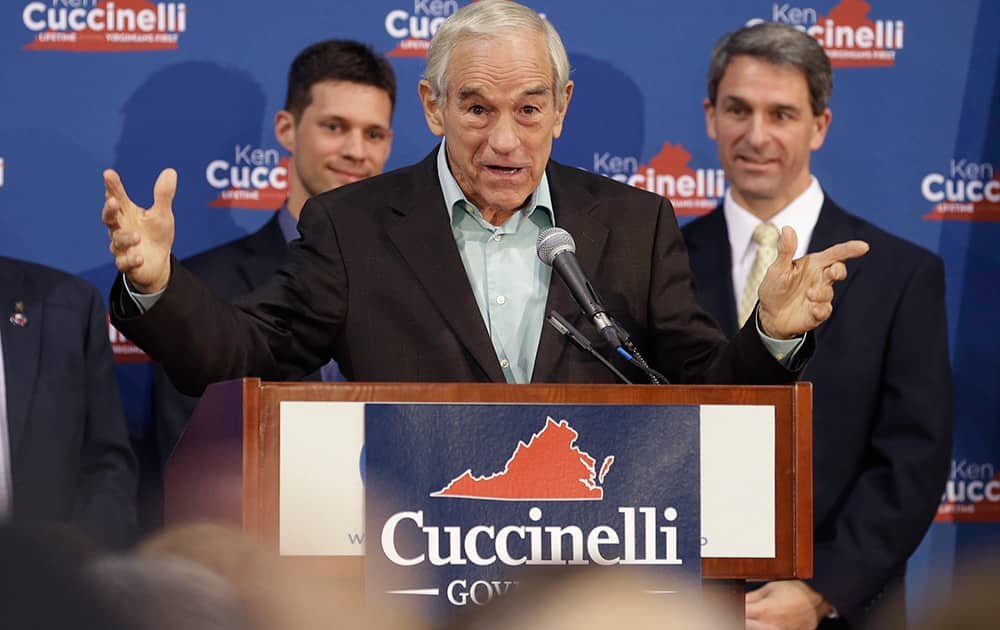Republican gubernatorial candidate, Virginia Attorney General Ken Cuccinelli, right, listens to former U.S. Rep. Ron Paul, center, during a rally in Richmond, Va.
