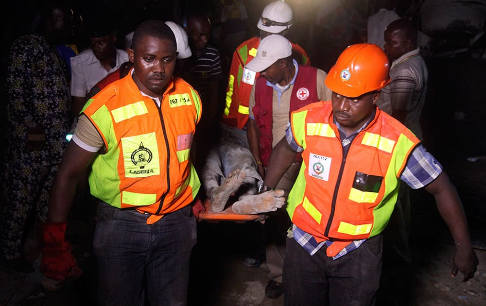 Rescue workers carry a survivor from the rubble of a building under construction which collapsed in Lagos, Nigeria. Emergency officials said casualty figures from the incident were unclear as they continued their search for survivors.