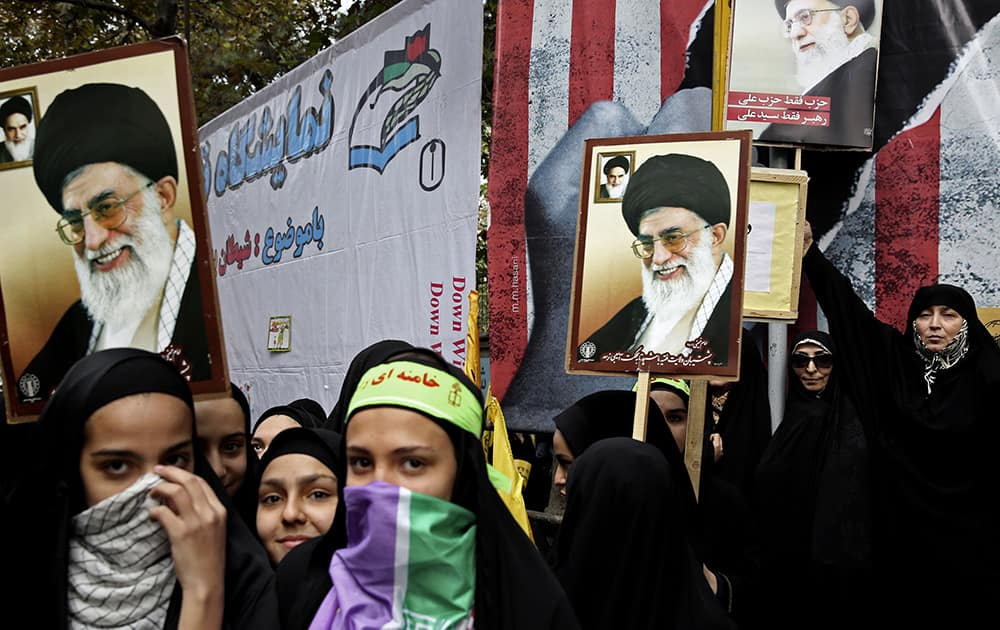 Iranian protesters hold posters with photos of supreme leader Ayatollah Ali Khamenei during an annual anti-American demonstration in Tehran, Iran.