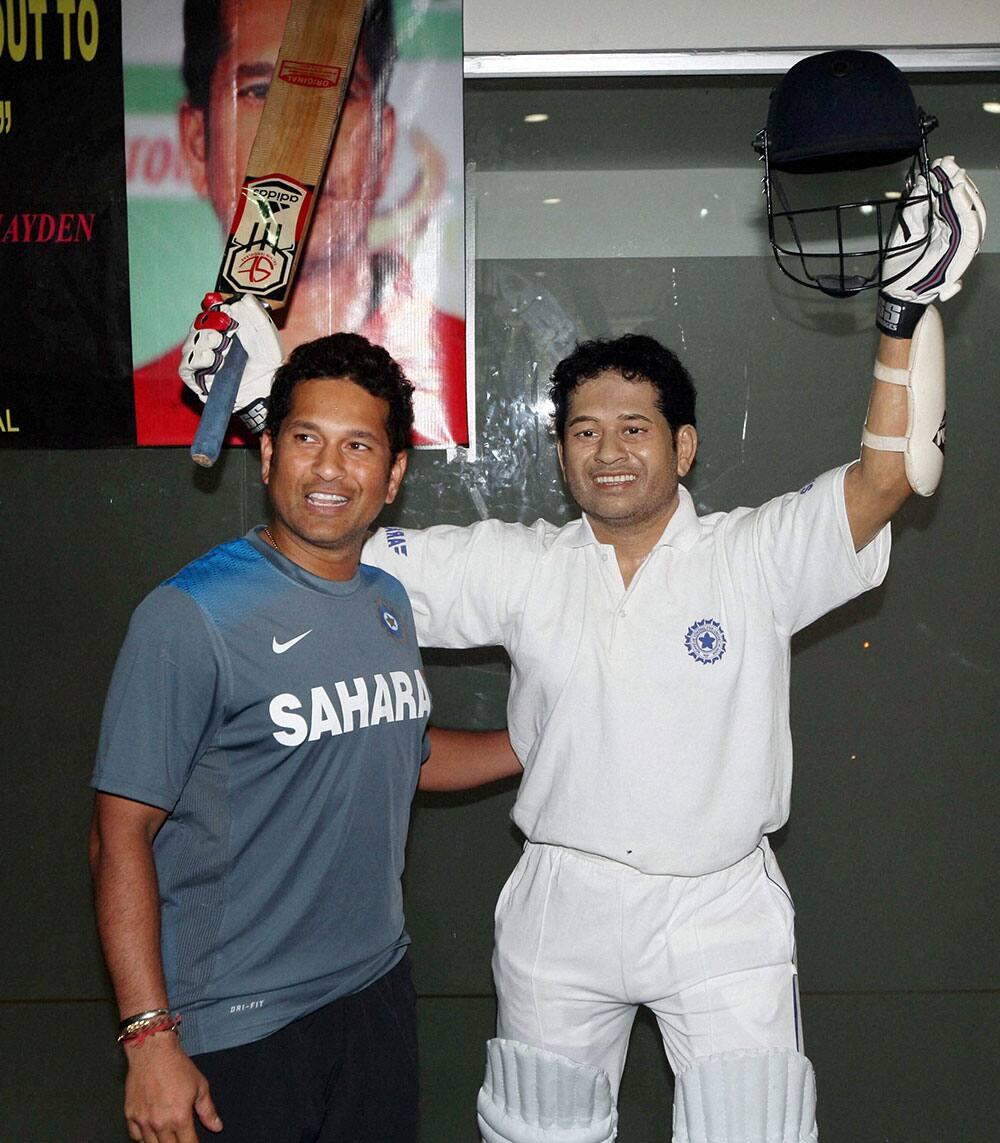 Cricketer Sachin Tendulkar stands in front of his life size wax statue at Eden Garden in Kolkata.