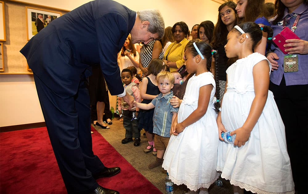 US Secretary of State John Kerry greets the children of US Embassy employees during a visit to the facility in Riyadh.