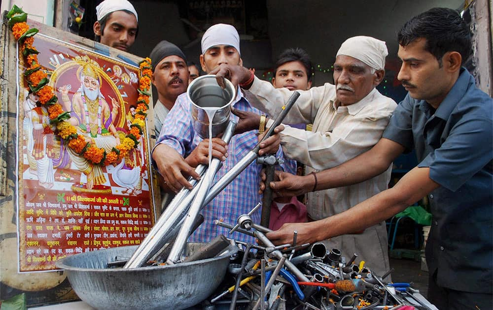 Artisans cleaning their tools with milk and performing puja on the occasion of Vishwakarma Day in Amritsar.