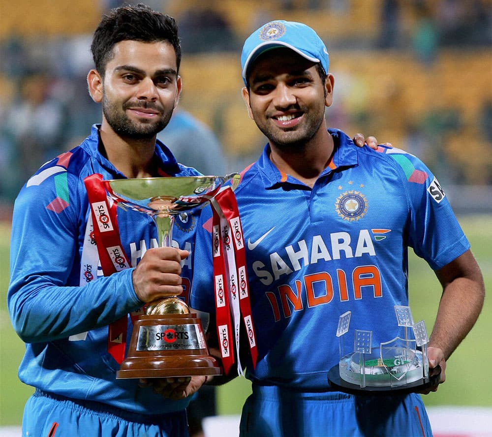 Indian players Rohit Sharma and Virat Kohli with the trophy after India beat Australia in the 7th ODI by 57 runs to win series 3-2 in Bangalore.