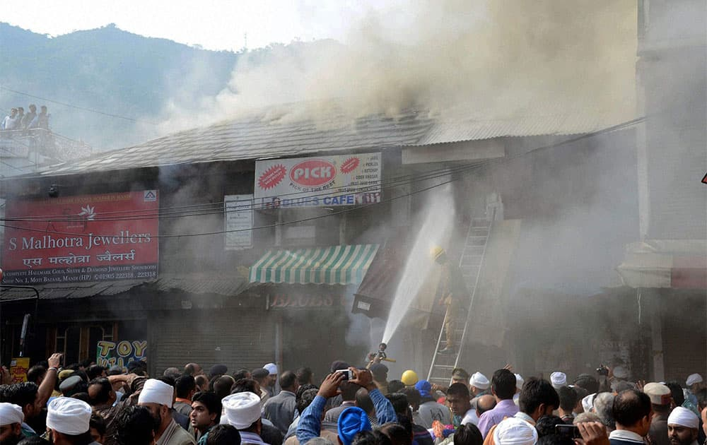 Firemen trying to douse the fire in Chohata bazar, Mandi.