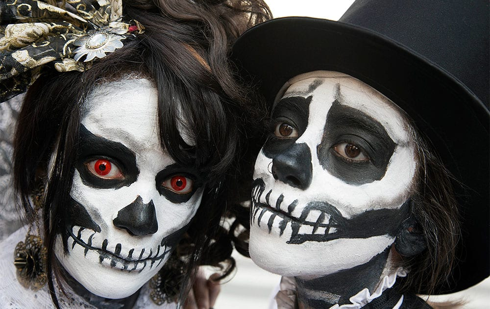 A woman and a man, painted up as calaveras or skull faces, pose for a photo during a Zombie Walk in Sao Paulo, Brazil.