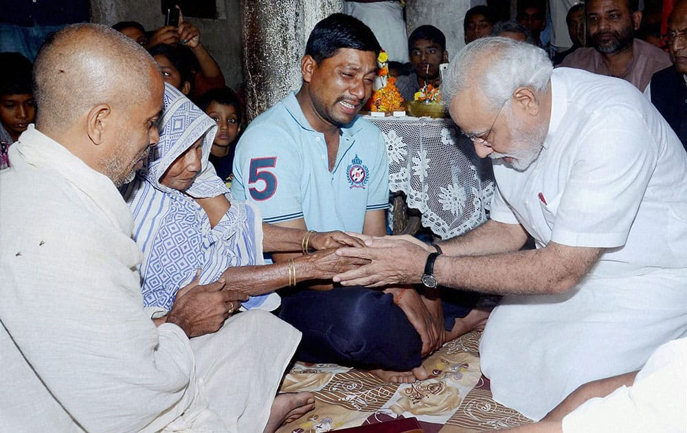 BJP`s Prime Ministerial candidate Narendra Modi consoles the family members of Rajnarian Singh, a victim of the recent serial bomb blasts, in Patna.