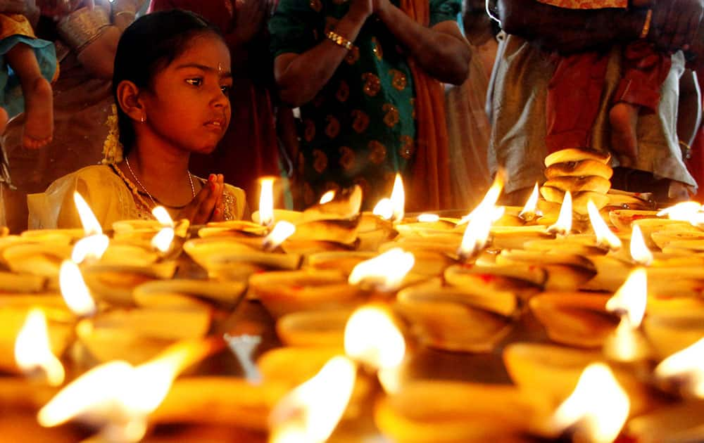 A Hindu devotee offers a prayer in front of oil lamps during Diwali, or the Hindu festival of lights at Batu Caves Hindu temple in Kuala Lumpur, Malaysia.