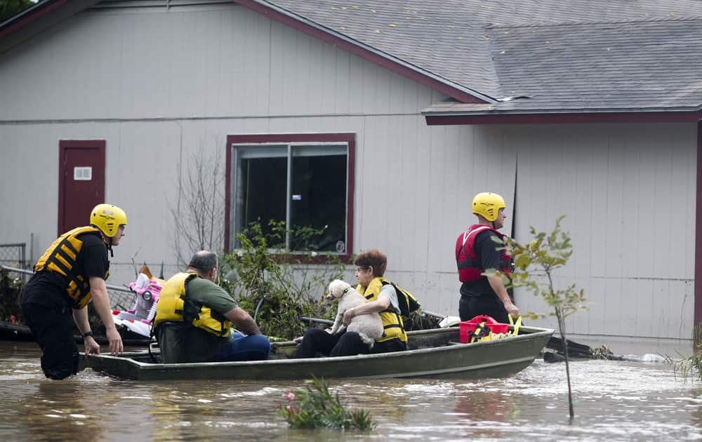 People are rescued from a home`s rooftop on Canella Drive in southeast Austin, Texas.