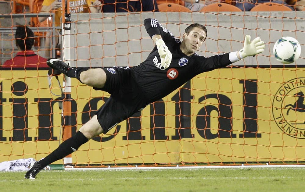Montreal Impact goalkeeper Troy Perkins makes a diving attempt on a shot that went wide in the first half against the Houston Dynamo during a knockout-round match in the MLS Cup soccer playoffs, in Houston.