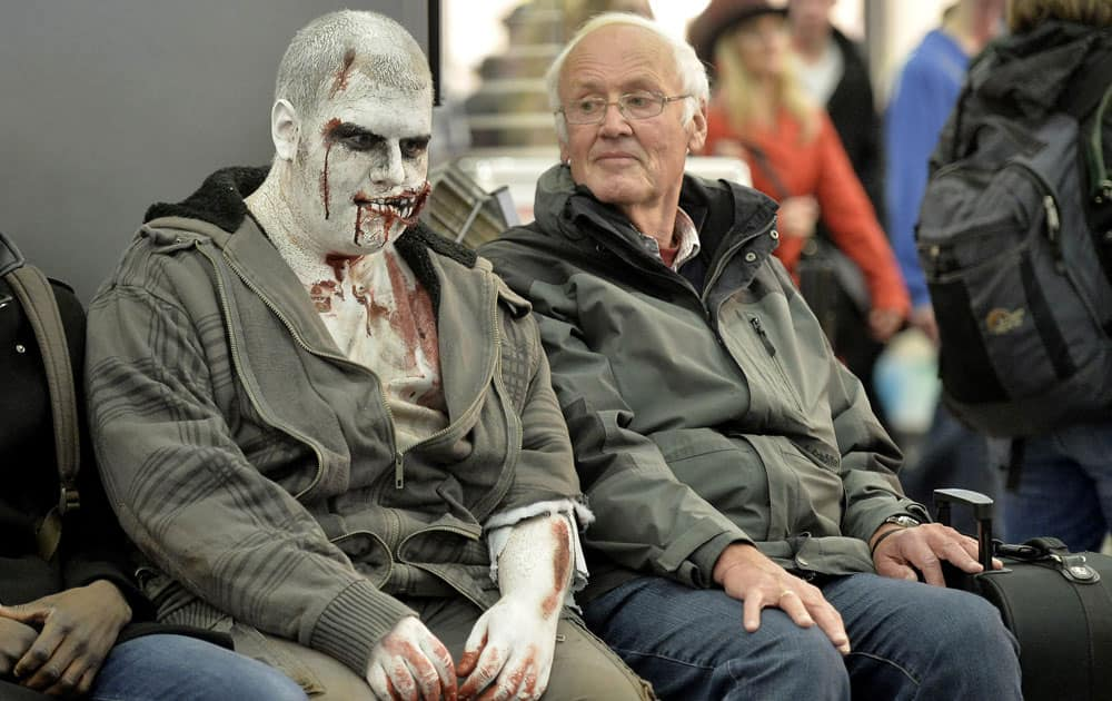 A man waiting at the train station looks at another wearing Halloween themed make-up in the city center of Essen, western Germany.