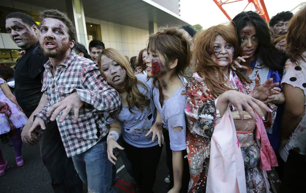 Former sumo grand champion Akebono, far left, and other participants wearing zombie makeups, perform during a Halloween event at Tokyo Tower in Tokyo.