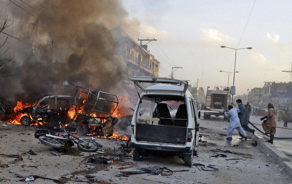 Pakistani firemen extinguish a fire on a burning vehicle at the site of a bomb blast in a market in Quetta.