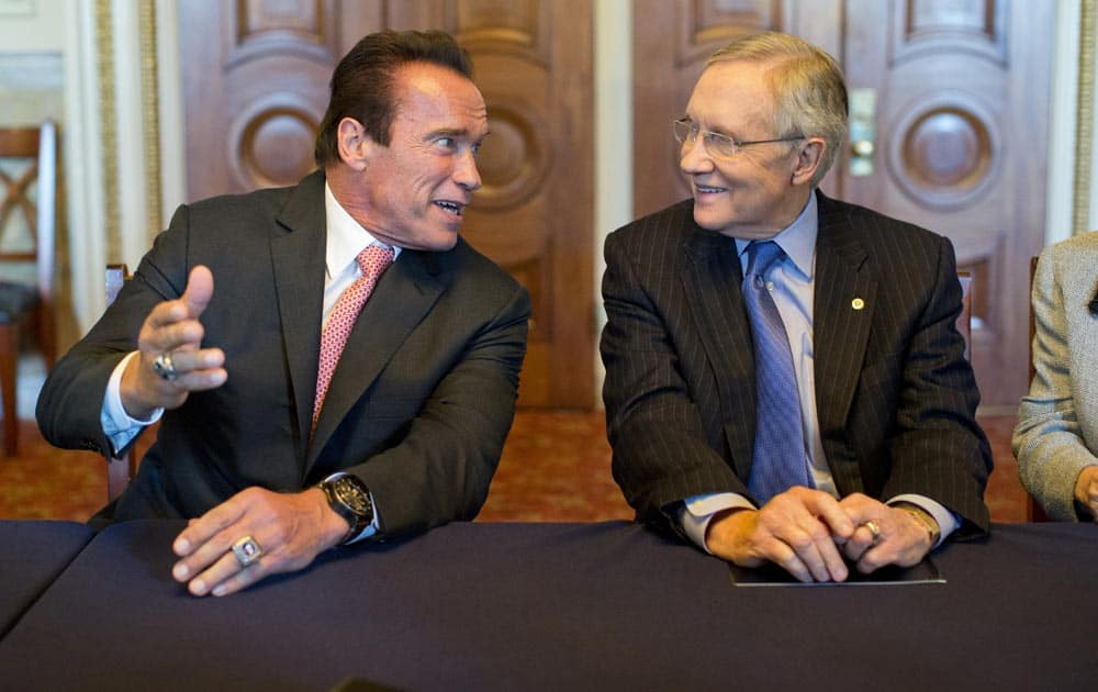 Former California Gov. Arnold Schwarzenegger, talks with Senate Majority Leader Harry Reid of Nev., before a meeting about funding after school programs, on Capitol Hill in Washington.
