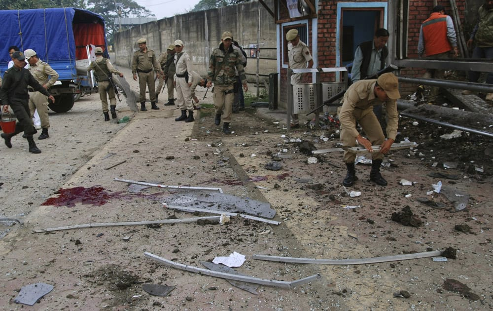 Security officers inspect the site after a crude bomb went off at a covered bus stop in Imphal, Manipur.