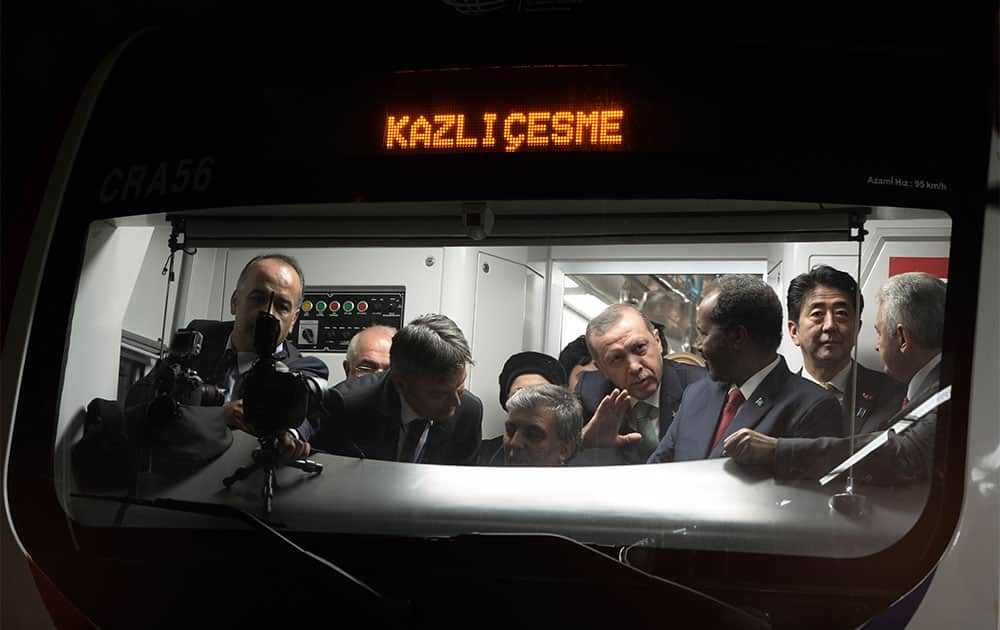 Japanese Prime Minister Shinzo Abe, second right, his Turkish counterpart Recep Tayyip Erdogan, fourth right, and other officials wait inside a train to cross the Bosporus after the inauguration of the tunnel called the Marmaray in Istanbul, Turkey.