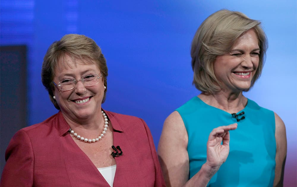 Presidential candidates Michelle Bachelet, left, and Evelyn Matthei, right, smile before the start of a debate at a television station in Santiago, Chile.
