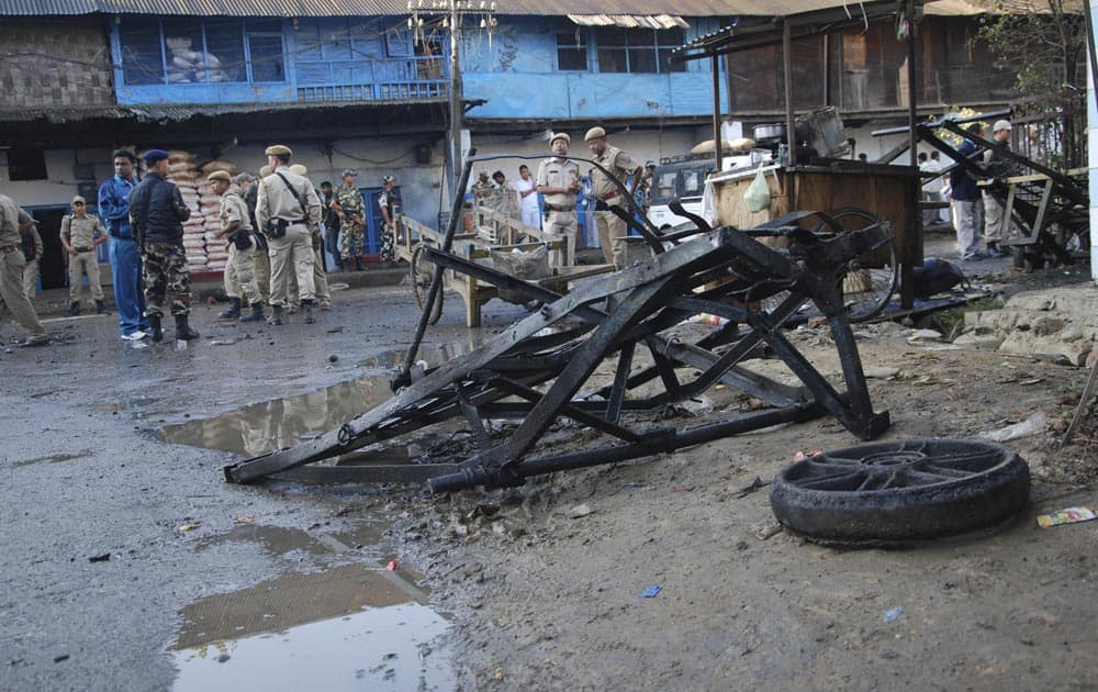 Security men stand at the site where a crude bomb exploded near the Khwairamband market in Imphal.