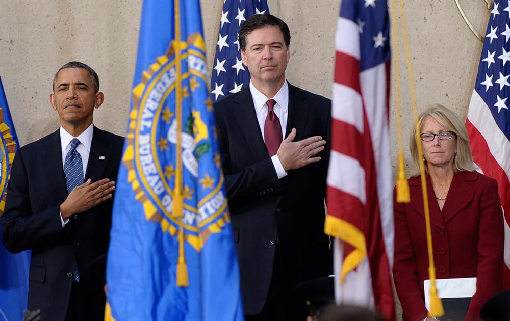 President Barack Obama stands with James Comey, center, and his wife Patrice Failor, right, during the singing of the National Anthem at Comey`s installation as FBI Director, at FBI Headquarters in Washington.
