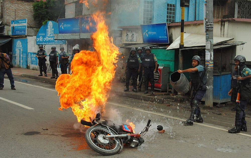 Bangladeshi police officers try to douse the flames on a motorcycle allegedly ignited by opposition activists during a general strike in Rajshahi, outskirts of Dhaka.
