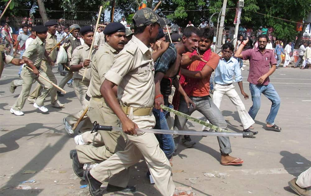 People thrash a man whom the police detain and take away for questioning after a bomb blast outside the venue of a political rally in Patna.