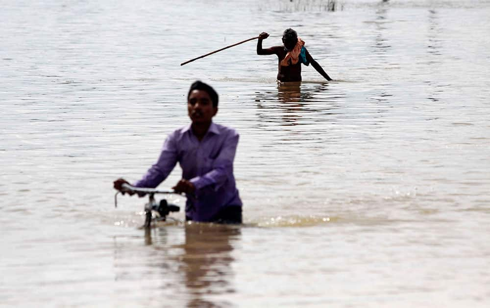 An Indian villager pushes his bicycle as an elderly man negotiates his way through floodwaters in Ganjam district of Orissa state, India.