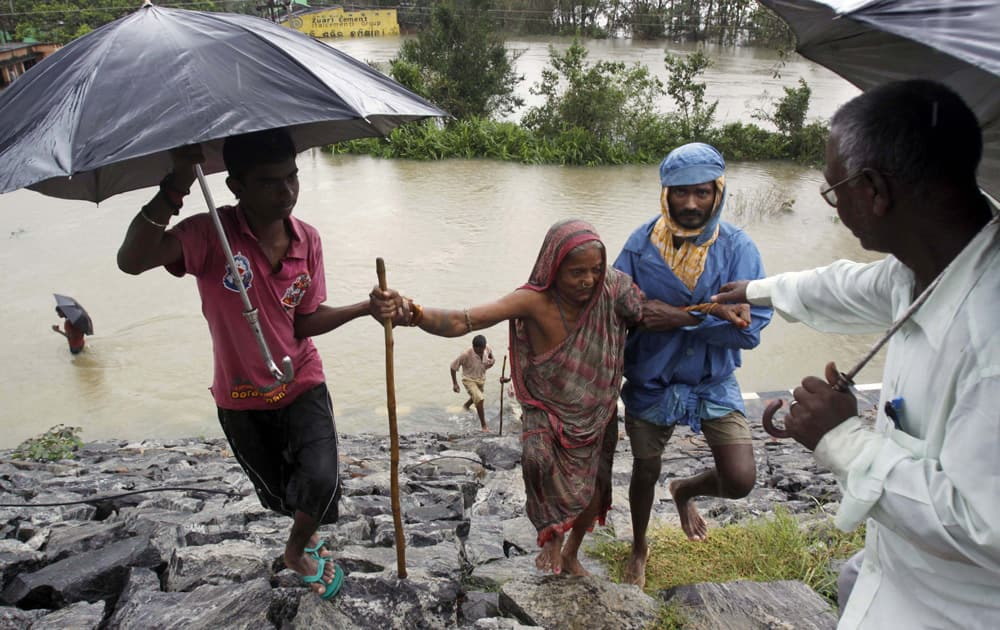 Villagers help an elderly woman to safer ground after crossing floodwaters in Khurda district, in the eastern Indian state of Orissa.