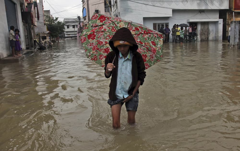 A boy holds an umbrella and wades through a flooded street in Hyderabad.