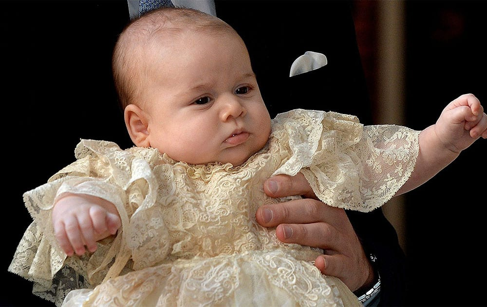Britain`s Prince George is held by his father Prince William as they arrive at Chapel Royal in St James`s Palace in London, for the christening of the three month-old Prince.
