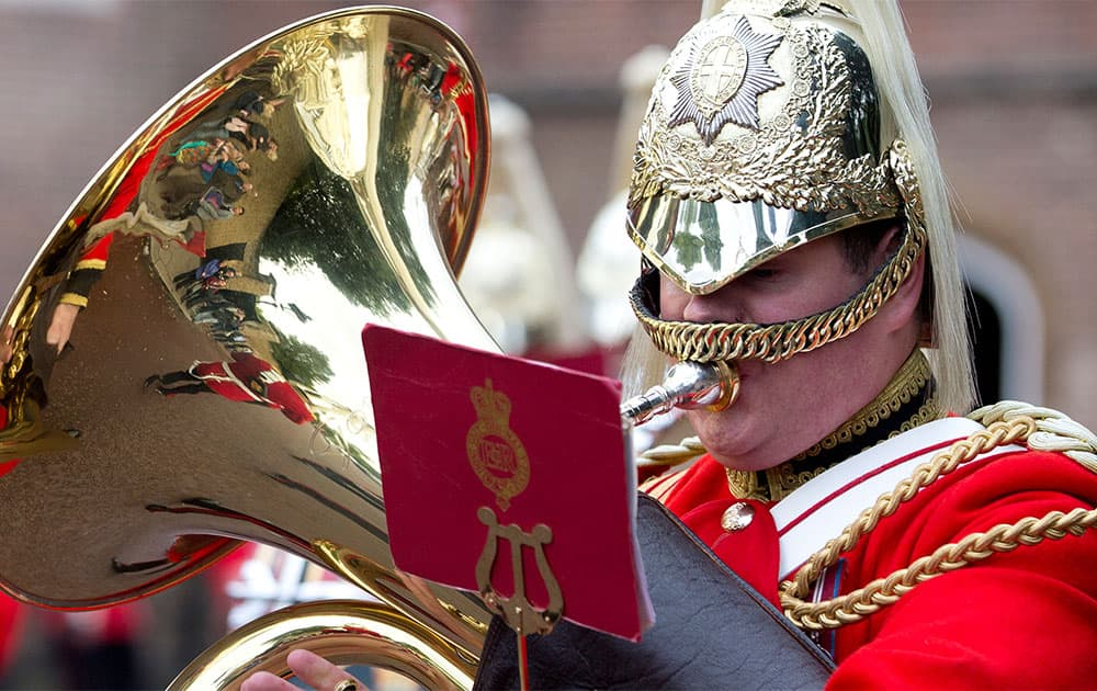 Tourists are reflected in the brass of a member of the Life Guards band as they escort a Colour party of the Grenadier Guards as they leave St James`s Palace to change the guard at Buckingham Palace in London.