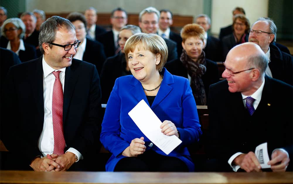 German Chancellor Angela Merkel, center, sits between Andreas Vosskuhle, left, president of the Federal Constitutional Court of Germany and Parliament President Norbert Lammert, right, as she attends an ecumenical service prior to a constitute session of the German parliament Bundestag in Berlin.