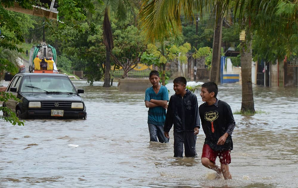 Young men play in a flooded street in Acapulco, Mexico.