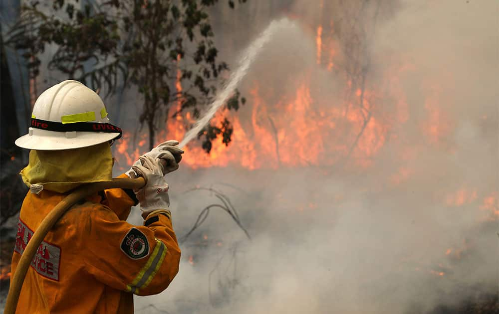 A firefighter tries to control flames near houses at Bilpin, 75 kilometers (47 miles) west of Sydney, Australia.