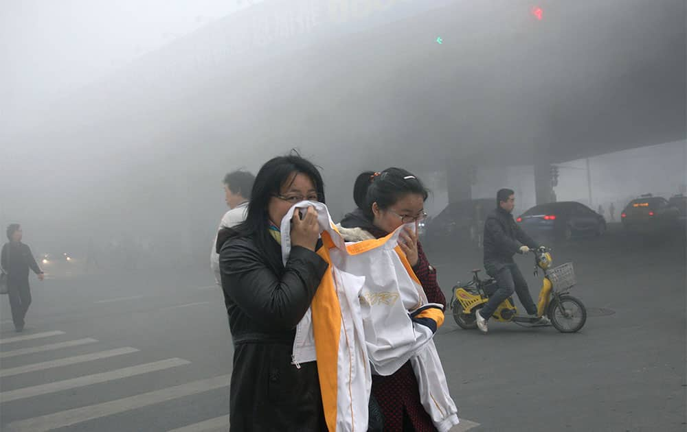 Two women cover up their mouths and noses with a jacket as they cross a street covered by dense smog in Harbin, northern China.