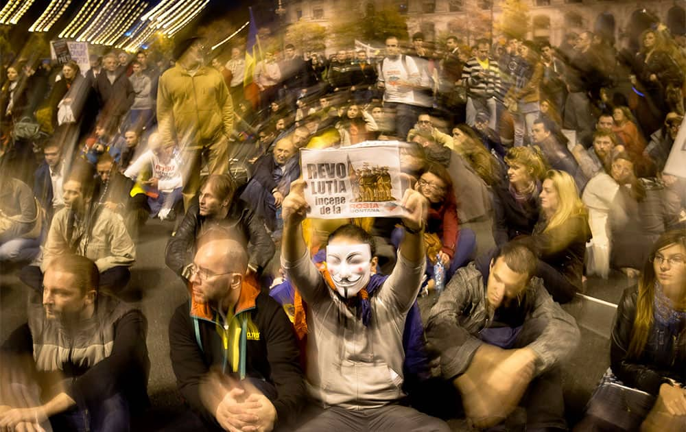 Protesters, one wearing a Guy Fawkes mask and holding a poster that reads