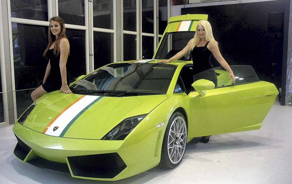 Models pose with a car during the Autocar Performance Show 2013 exhibition in Mumbai.