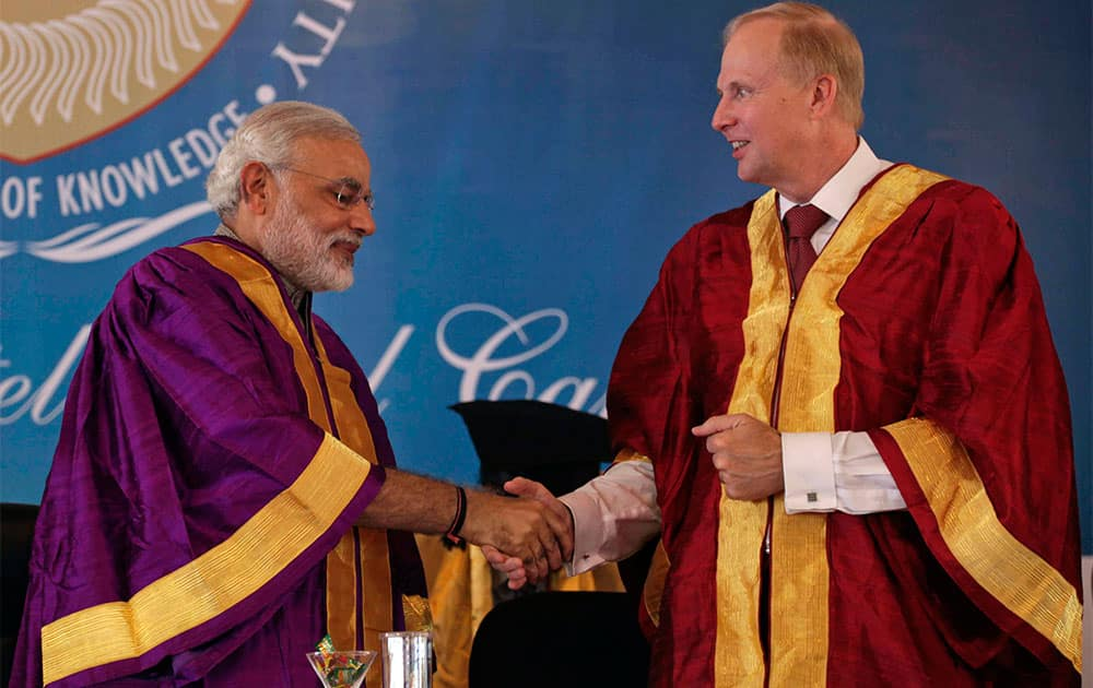 Gujarat state Chief Minister Narendra Modi, left, shakes hand with British Petroleum Group Chief Executive Bob Dudley during the convocation ceremony of Pandit Deendayal Petroleum University (PDPU) in Gandhinagar, in the western Indian state of Gujarat.