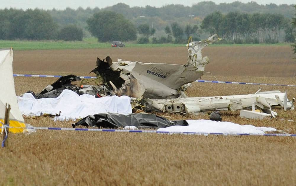Bodies are covered near the debris of a small plane which crashed in a field in Marchovelette, Belgium. The plane, carrying parachutists for a skydiving trip, crashed killing all 11 people aboard, officials said.
